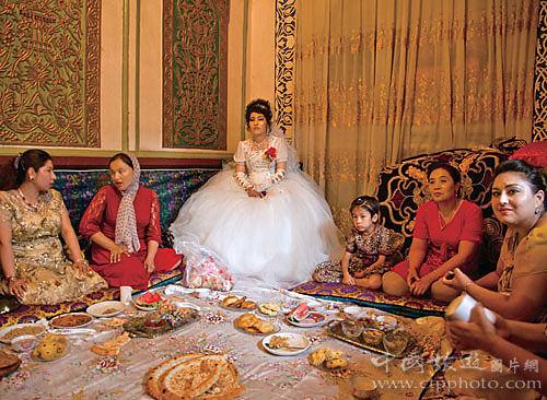 一名维吾尔新娘穿婚纱,在亲朋好友的陪伴下等待新郎前来迎亲(谢光辉摄)