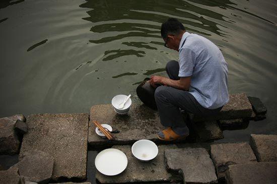 在小溪边洗碗的老人