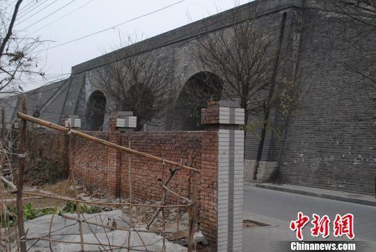 图为一道漂亮的灰白围墙隔开的两样景色。 冀浩凡 摄