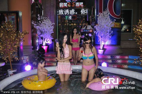 2013年8月16日,武汉闹市街头,几位身着比基尼的美眉在充气泳池中戏水清凉亮相,为酒吧派对吸睛。图片来源:CFP