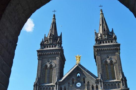 教堂前面是三扇拱门,两侧有成排的小窗