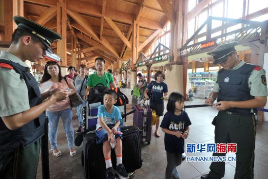 8月19日,三亚凤凰边防检查站的干警在凤凰机场查验旅客证件。