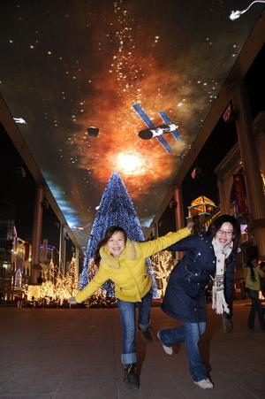 两位女青年在北京世贸天阶里的圣诞树前玩耍。新华网 文涛 摄
