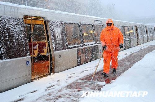 3月2日,在美国弗吉尼亚州维也纳的一个城铁站台上,一名工人清扫积雪。新华社/法新