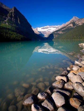 """公园里的路易斯湖因为""""岩石粉""""而呈现出深祖母绿色。""""岩石粉""""卷着水面上的冰块顺流而下。"""
