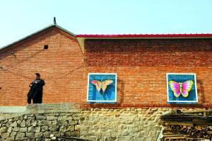 刚到村口,就已经看到砌在农家院墙外的铁制风筝模型。