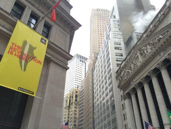 """在纽交所对面,颇有年头的洛克菲勒式建筑上垂下一面醒目旗帜,上面写着""""革命来了!"""""""