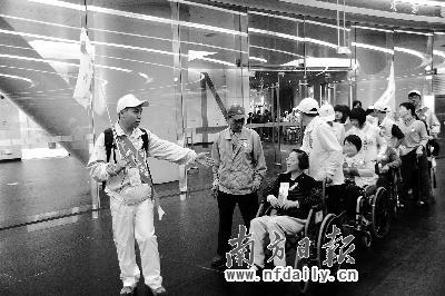 """志愿者""""一对一""""陪同残疾人参观广州塔。"""