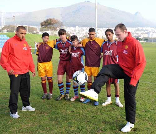 图文-曼联在南非与小球员互动亲自示范颠球的技巧