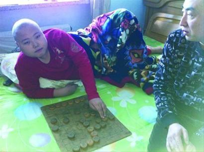 做度过募化疗的刘洋头发曾经掉落光,躺在病床上还在切磋棋谱,他最父亲的期望是和中国象棋巨万匠对弈。 记者 徐方 摄