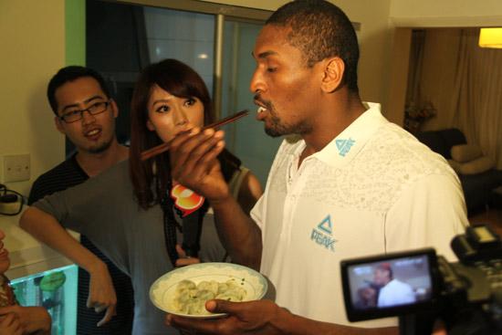 图文-阿泰现身球迷家尝试包饺子美女目不转睛