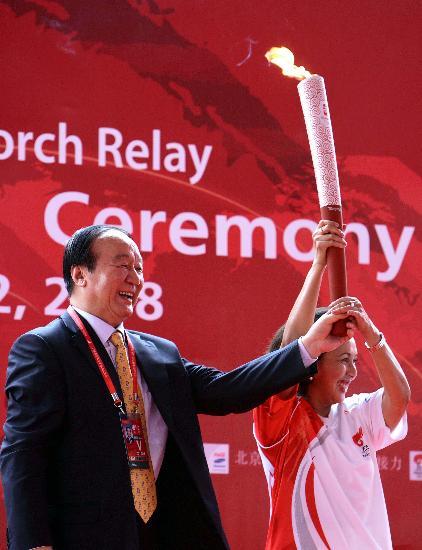 图文-奥运圣火在印尼雅加达传递 蒋效愚交接火炬