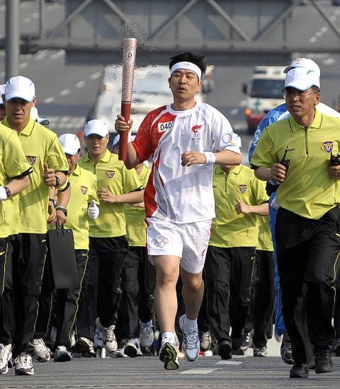 图文-北京奥运圣火在首尔传递 朴钟新手持火炬传递