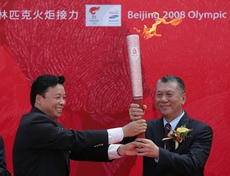 图文-奥运圣火在澳门传递 杨树安将火炬交给何厚铧