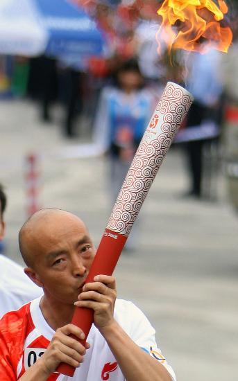 图文-奥运圣火在云南昆明传递 漆光伟亲吻火炬