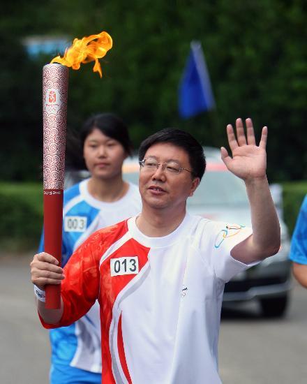 图文-奥运圣火在云南昆明传递 火炬手张晓军挥手