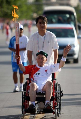 图文-北京奥运圣火在喀什传递 艾约甫手持火炬传递