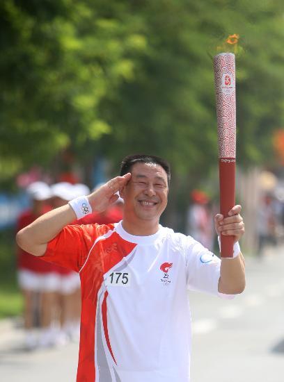 图文-奥运圣火在吴忠传递 火炬手冯建军手持火炬