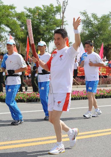 图文-奥运圣火在吴忠传递 火炬手夏林手持火炬传递