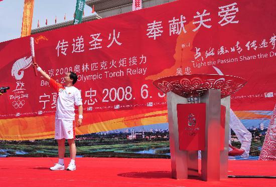 图文-奥运圣火在吴忠传递 火炬手主席台上展示火炬