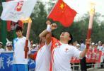 图文-北京奥运圣火在沈阳传递 杜俊峰与杜荣杰交接