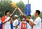图文-北京奥运圣火在沈阳传递 郭士强与楚金玲交接