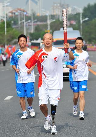 图文-奥运圣火在鞍山传递 裴莽手持火炬进行传递