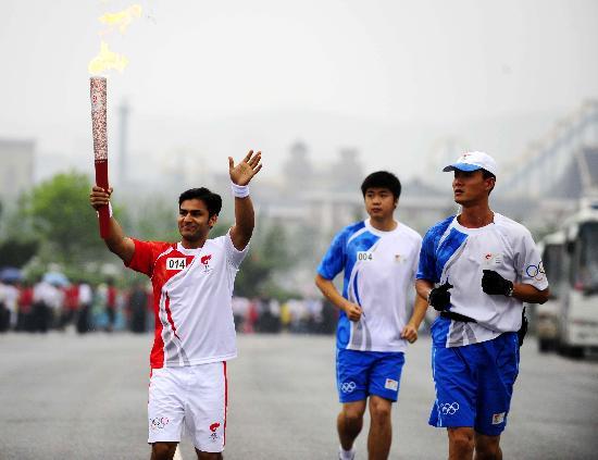 图文-奥运圣火在大连传递 外籍火炬手雷斯挥手