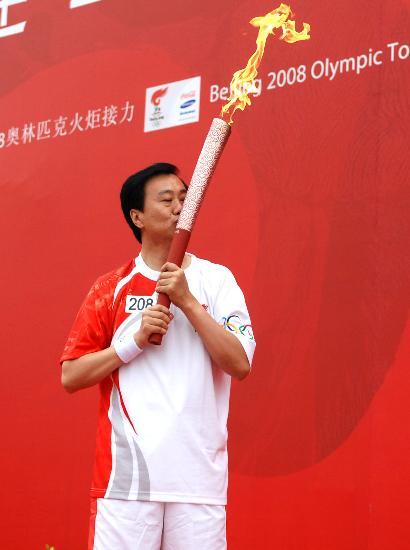 图文-北京奥运圣火在大连传递 夏德仁亲吻火炬