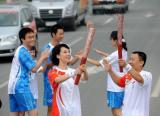 图文-奥运圣火在济南传递 火炬手陈虎与李毅交接