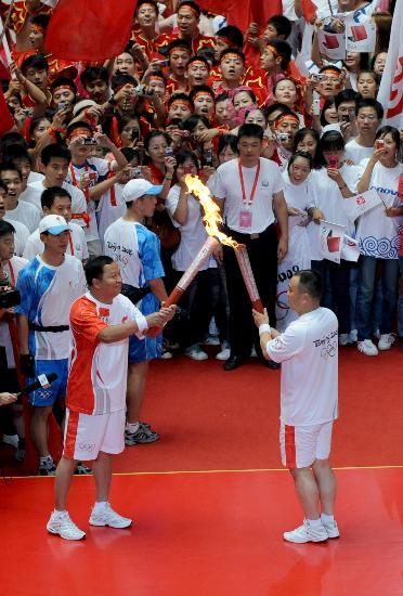 图文-奥运圣火在郑州传递 万众瞩目中交接圣火