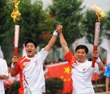 图文-奥运圣火在洛阳传递 火炬手交接联手高呼