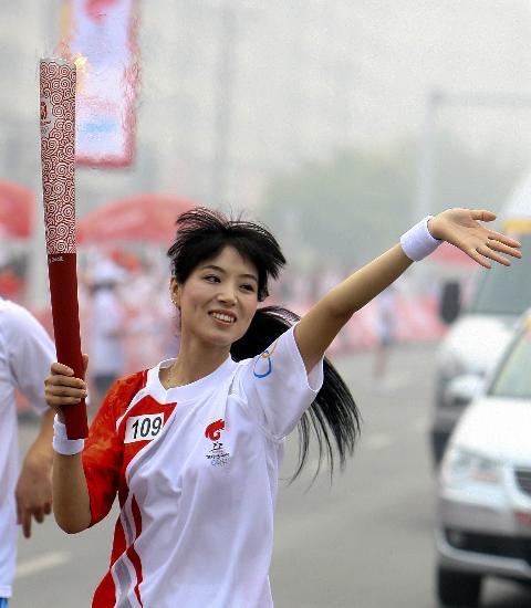 图文-北京奥运圣火在安阳传递 张佳手持火炬传递