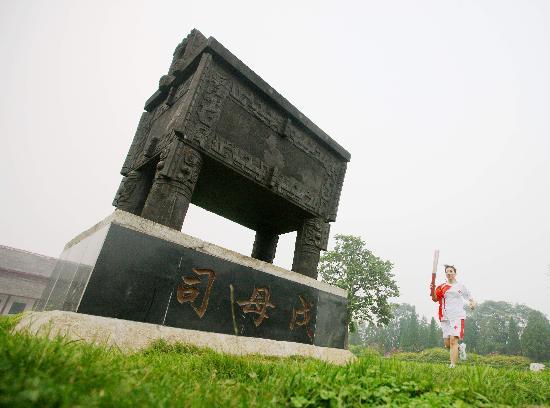图文-奥运圣火在安阳传递 在司母戊鼎雕塑前传递