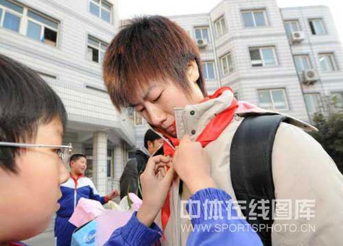 图文-张怡宁丁宁小学生打乒乓球指点戴上红领门球球直径图片