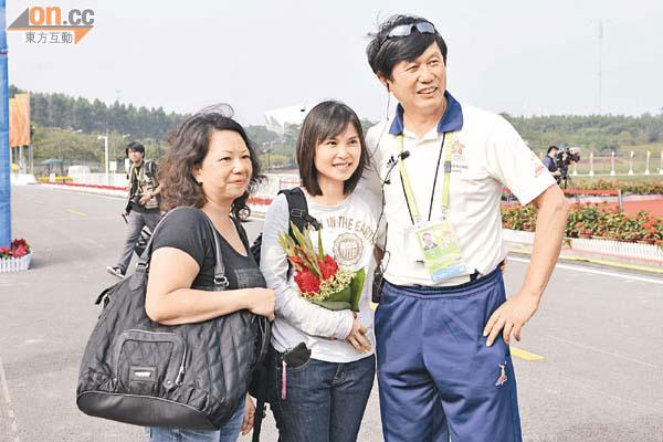 夺冠后,手捧黄金宝夺冠鲜花的女友与教练沈金康合影(图片来源:香港太阳报司徒子文摄)
